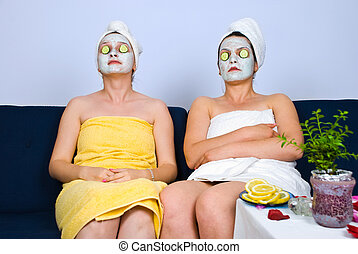 Two women with facial mask at spa - Two women sitting on...