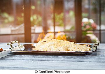Burning fish on tray.