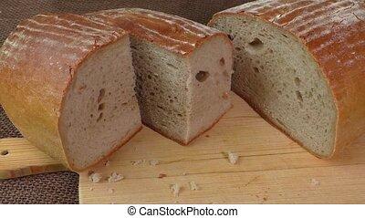 Cut loaf of fresh bread on burlap