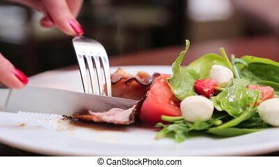 Eating salad with fork and knife close up