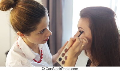 Make-up artist work on her friendReal people