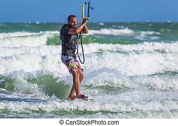 Athletic man riding on kite surf board sea waves - Athletic...