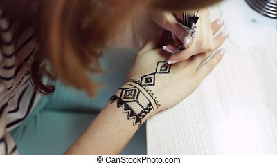 Henna tattoo on women hands - Artist applying henna tattoo...