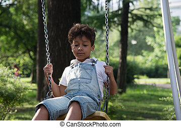 afro american school boy having fun on a swing - afro...