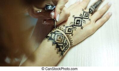 Henna tattoo on women hands - Artist applying henna tattoo...
