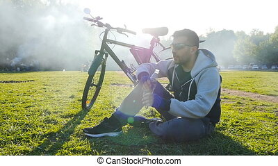 Cyclist is drinking water from the bottle