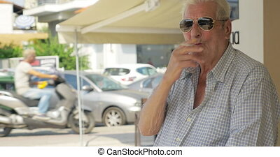 Smoking senior man in the street - Aged man in sunglasses...