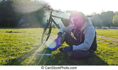 Cyclist is drinking water from the bottle - Cyclist is...