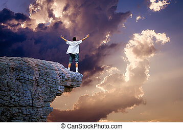 Man standing on cliff above cloudy sky - Man on top of...