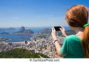 girl tourist takes a picture of Rio landscape with...