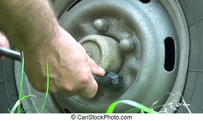 Mechanic Hands Replace Car Tire Outdoor. Closeup. - Mechanic...