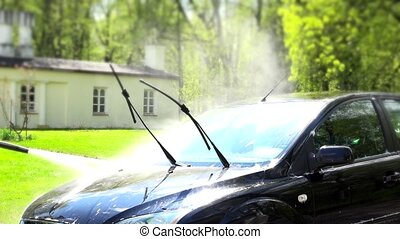worker washing automobile with high pressure water jet in house yard.