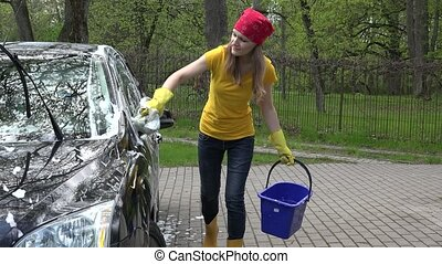 Pretty woman washes her car with sponge in open air. -...