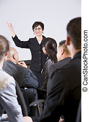 Hispanic woman speaking to group of businesspeople -...