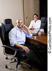 Mid-adult Hispanic office workers in boardroom