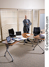 Mid-adult Hispanic businessman standing in office