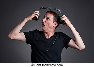 Man with a headphone - A middle age man holding away the...