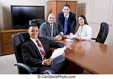 Hispanic business people meeting in boardroom, focus on man...