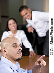 Hispanic business people in boardroom watching
