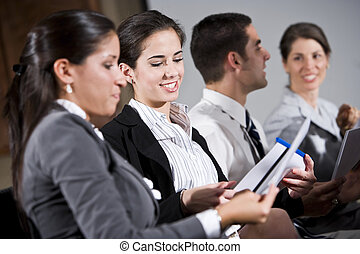 Young woman sitting in row reading report - Young business...