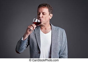 Man with glass of wine - A middle age man drinking and...