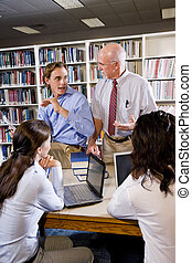 College professor with students talking in library - College...