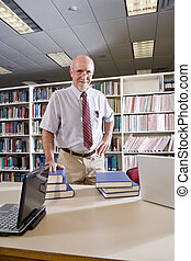 Portrait of mature man at library table with textbooks