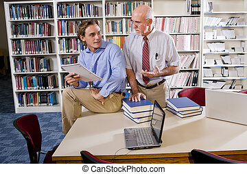 College professor with student talking in library - College...