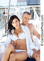 Handsome man and a beautiful and sexy woman on a sailing...