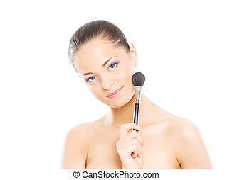 Portrait of a young woman holding a makeup brush - Beauty...