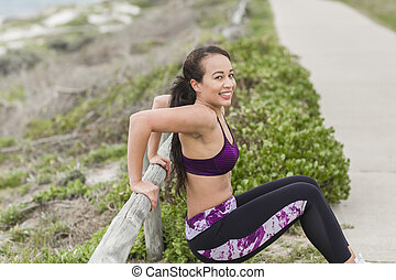 Young fit female working out outside during cloudy winter day. Smiling beatiful girl