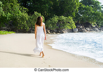 Attractive, young woman walking on the coast