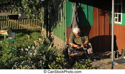 Man repairing a lamp near the house, change the wire around a country house