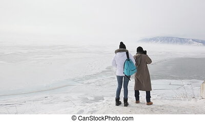 Couple travelers visiting lake with mountains in winter and take pictures.