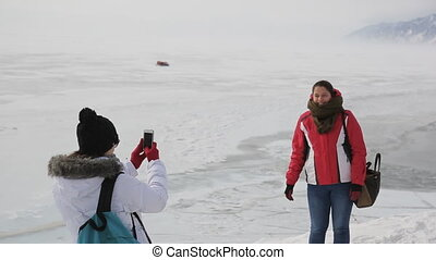 Two women tourists are photographed on a background of icy lakes and mountains.