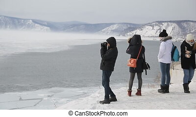 A group of young tourists visit winter lake in mountains and take pictures of landscape.