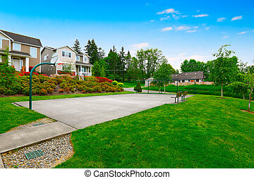 Small sports court near the house with green lawn View of...