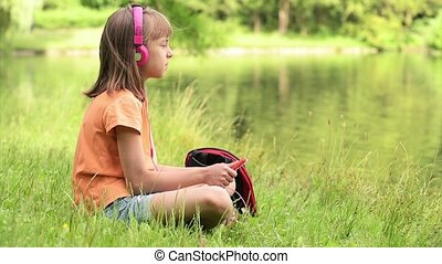 Little girl at lakeside - Little girl with tablet pc and...