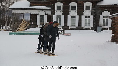 Group of people tries to move on one pair of wooden skiing....