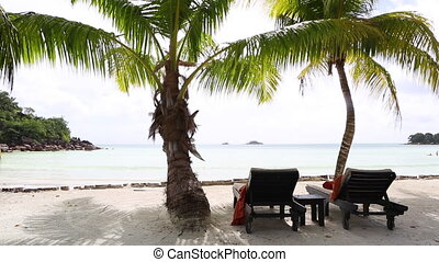 Deckchairs at tropical landscape view at Prasin island,...