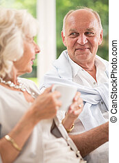 Relaxation with tea - Elderly couple sitting on couch and...