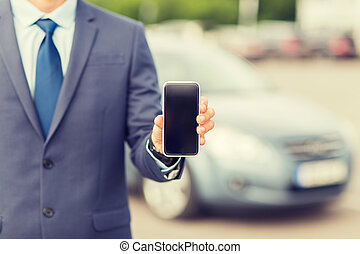 close up of business man with smartphone and car -...