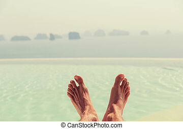 closeup of male feet over sea and sky on beach - summer...
