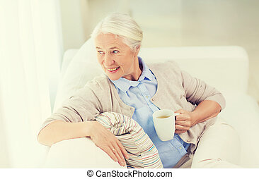 happy senior woman with cup of tea at home