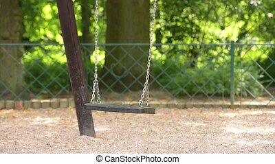 Swing swaying in park - Swing on the chains swaying in a...