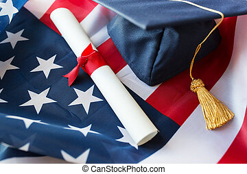 mortarboard and diploma on american flag - education,...