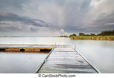wooden pier on big lake and clouded sky