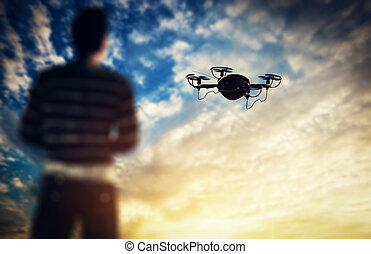 Man operating a drone at sunset. Aerial videography job. 3D...