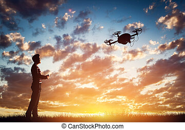 Man operating a drone at sunset. - Man operating a drone at...