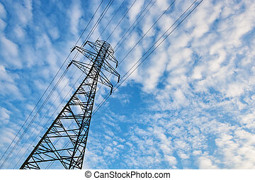 Electricity transmission pylon against blue sky with fluffy clouds